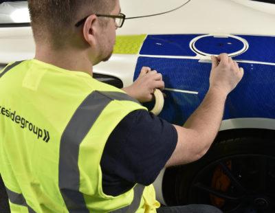 Man applying reflective vinyl to police car